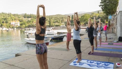 osoby uprawiające jogę w doku, nad wodą.