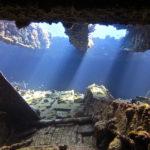 widok podwodny z wnętrza wraku Rosalie Moller. Promienie słońca wpadają przez dziury w pokładzie.