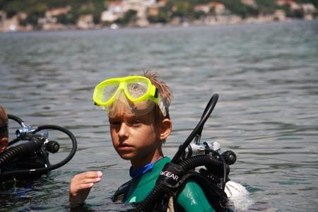 młody nurek, chłopiec w wieku szkolnym-podstawówkowym, wynurzający się z wody