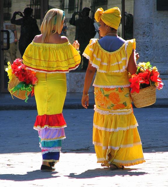 Ilustracja: wyjazd na Kubę, dwie tradycyjne sprzedawczynie kwiatów w barwnych, żółtych sukienkach, z koszami pełnymi kwiatów.