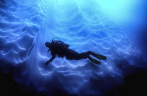 Diver against a fluted wall of ice.